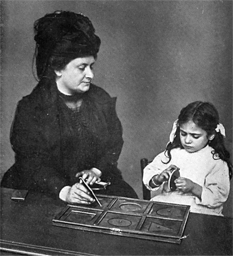 Maria Montessori bir kız çocuğunu geometri dolabının bir çekmecesiyle çalıştırırken.